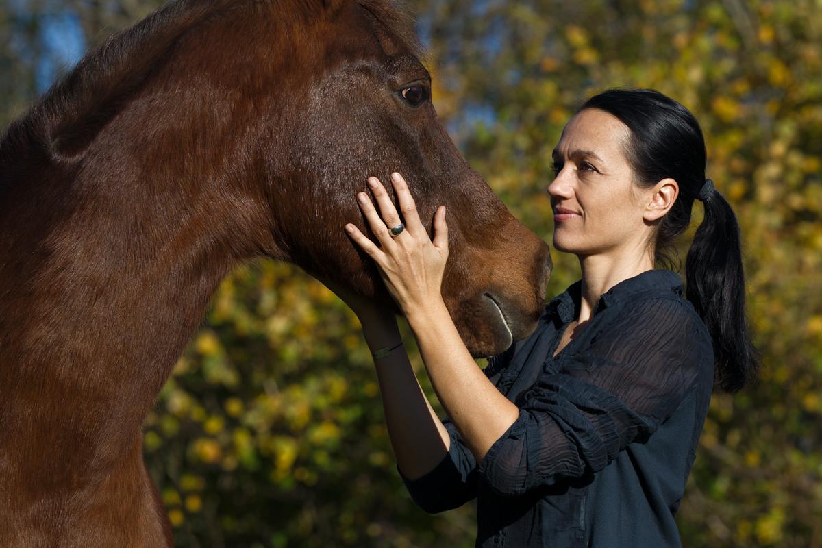 Julia Moll Pferdefotografin streichelt ein braunes Pferd während eines Fotoshootings